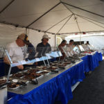 Event patrons serving themselves BBQ ribs from aluminum trays