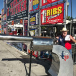 Man poses in front of Texas Thunder BBQ booth polished steel revolver