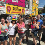 Group of event goers pose in front of large BBQ rib booth