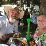 Couple with tall drink and BBQ ribs pose at a picnic table