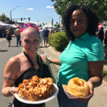 Two women pose with plates of food