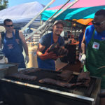 Three men grilling ribs